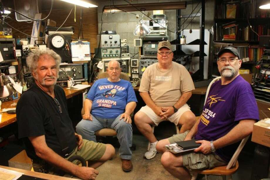 "Sam Neal (second from left) sits in his ""classroom"" where he aids eager students in studying for their entry level licenses, along with members of the Sam Houston Amateur Radio Klub. From left to right are Jimmy Hedricks, Neal, President Jeff McClain and Kenneth Luning. Photo: JACOB MCADAMS"
