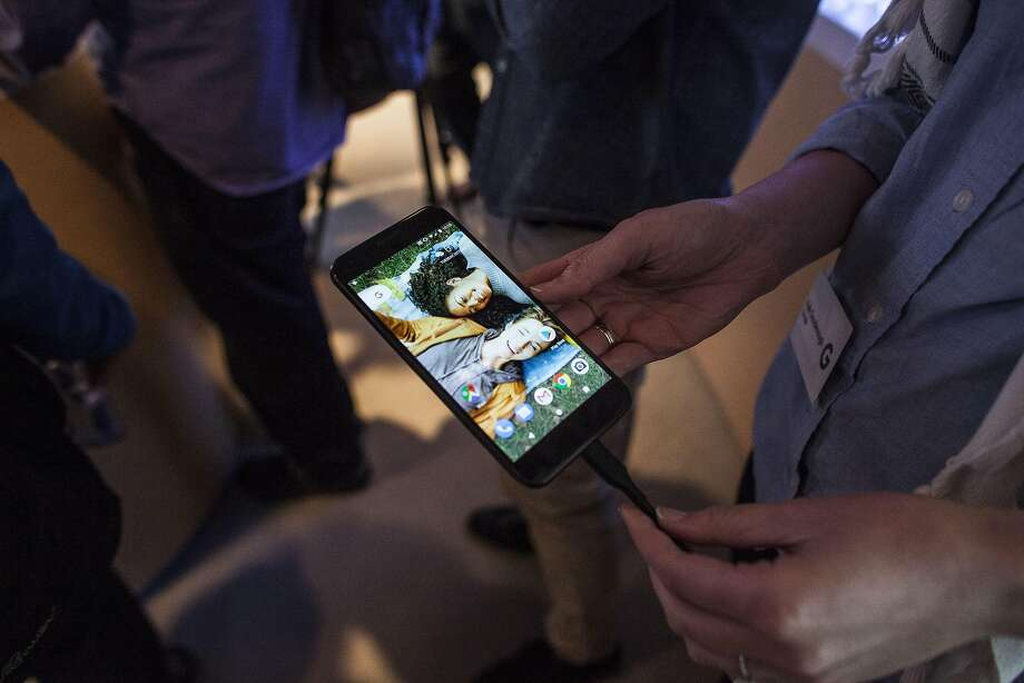 Members of the media examine Google's Pixel phone, manufactured by Taiwan's HTC, during an event to introduce Google hardware products in 2016. Google is buying HTC's Pixel phone-making business and taking on about 2,000 HTC employees in a $1.1 billion deal. Photo: Ramin Talaie, Getty Images