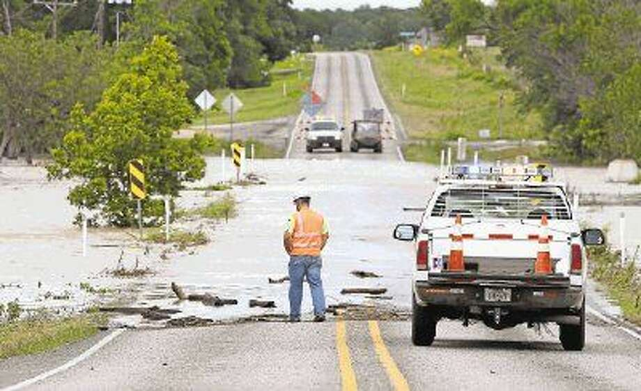 May was the wettest month in Texas history. Cody Ogle, with TxDot, at one side of the roadblock on FM 730 in Boyd, the West Fork of the Trinity River flowing over the road behind him as areas flood around Boyd, Texas, Saturday, May 30, 2015. (Paul Moseley/The Fort Worth Star-Telegram via AP). Photo: Paul Moseley