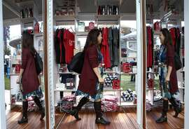 A woman shops in the (RED) pop-up store at the Dreamforce conference in San Francisco, Calif. on Tuesday, Oct. 4, 2016. Proceeds from the products go to AIDS research.