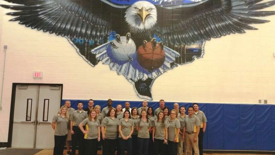 The Memorial Hermann Northeast Hospital athletic physicals team gathers under the New Caney High School Eagle before completing athletic physicals and EKG screenings at New Caney High School. The athletic physicals team traveled to nine middle schools and high schools and conducted athletic physicals on more than 4,000 student-athletes, and administered EKG screenings to more than 1,500 student-athletes since March.