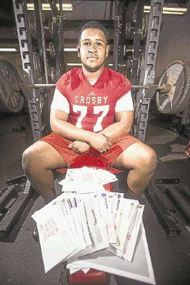 Cougars offensive lineman Keenan Murphy poses for a portrait with a portion of his collection of letters from universities across the country showing interest in his football abilities March 10, 2015, at Crosby High School. Photo: ANDREW BUCKLEY