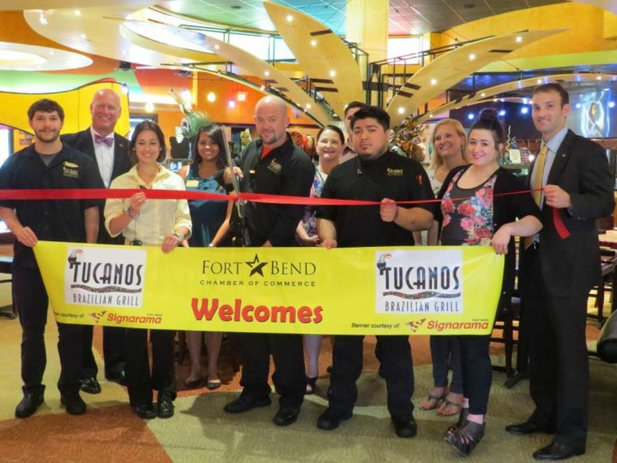 Robert Kelly, general manager of Tucanos Sugar Land, cuts the ribbon with staff and the Fort Bend Chamber of Commerce.