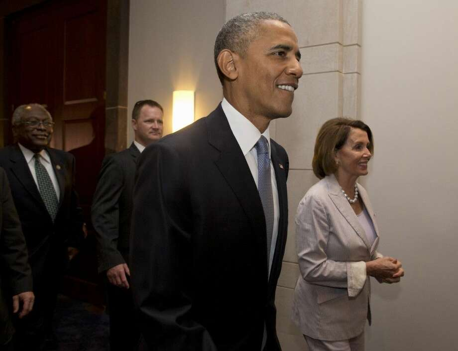 President Barack Obama, House Minority Leader Nancy Pelosi of Calif. and House Minority Assistant Leader James Clyburn of S.C., leave meeting with House Democrats on Capitol Hill in Washington, Friday.
