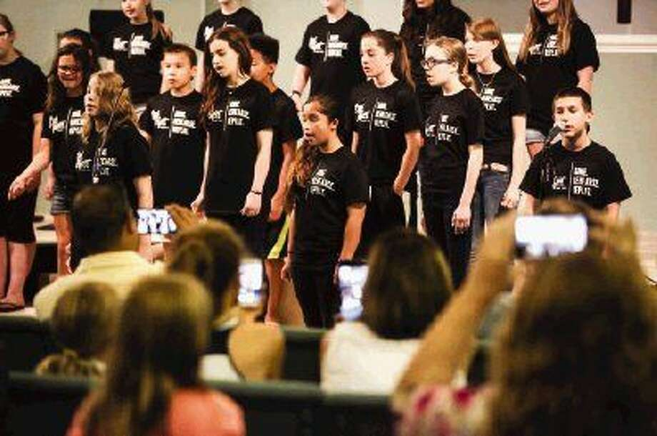 Parents film from the audience as students sing in the Pitch Perfect a capella camp on Friday at Oak Ridge Christian Academy.