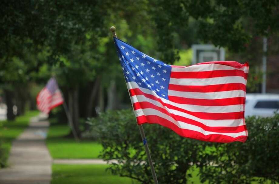 American flags fly in front of homes for the Fourth of July holiday on Rice Boulevard in West University Place. Photo: Alan Warren