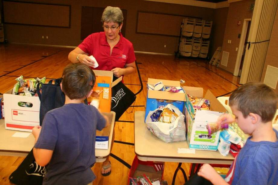 "Jill Parks helps two young volunteers stuff backpacks for ""Sacks for Soldiers"" at the LDS Church stake in Eagle Springs June 12, 2015."