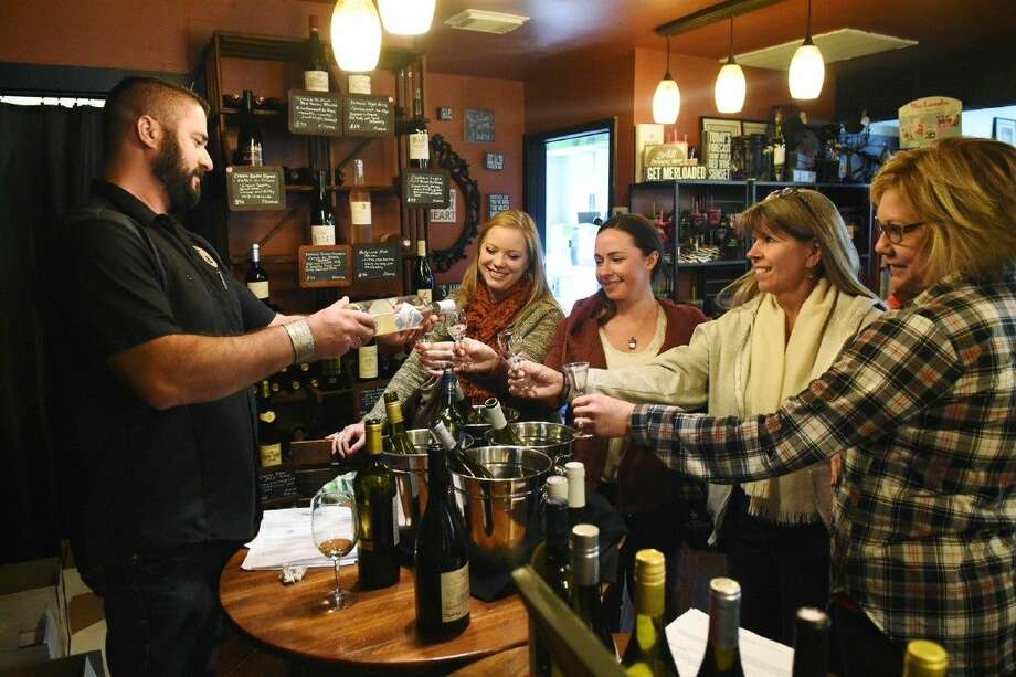 Brian Cox helps customers sample some French wines at a free wine tasting held at the Envy Wine Room in Old Town Spring on Saturday, Feb. 6.