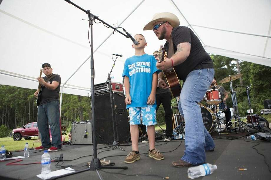 Jayce Ward, center, sings alongside his dad Josh as the Josh Ward Band performs during the Frazier girls benefit Saturday at Splendora High School. Proceeds from the event benefit the two daughters of Bradley and Shea Frazier, who both died in an accident in May.