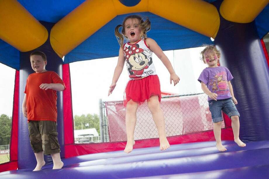 Kids leap in a bounce house during the Frazier girls benefit on Saturday at Splendora High School. Proceeds from the event benefit the two daughters of Bradley and Shea Frazier, who both died in an accident in May.