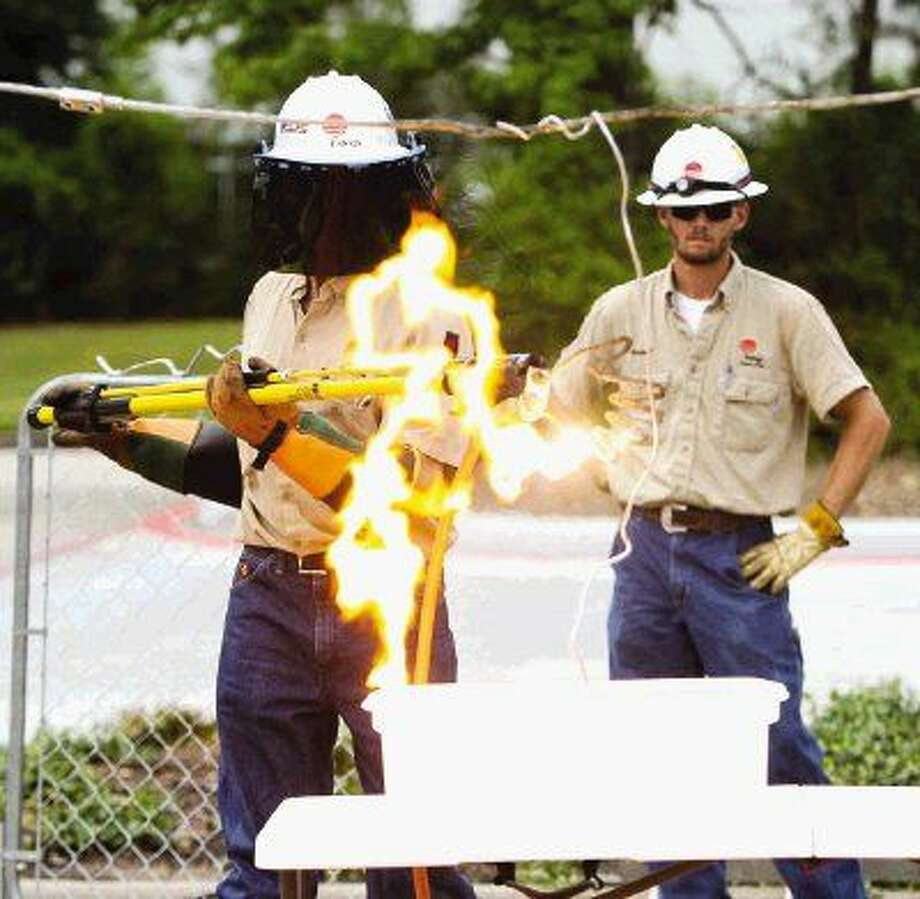 Entergy employees demonstrate what happens when a person touches a power line that has fallen into a pool during The Woodlands Emergency Preparedness Event Saturday. Go to HCNpics.com to view more photos from the event. Photo: Jason Fochtman