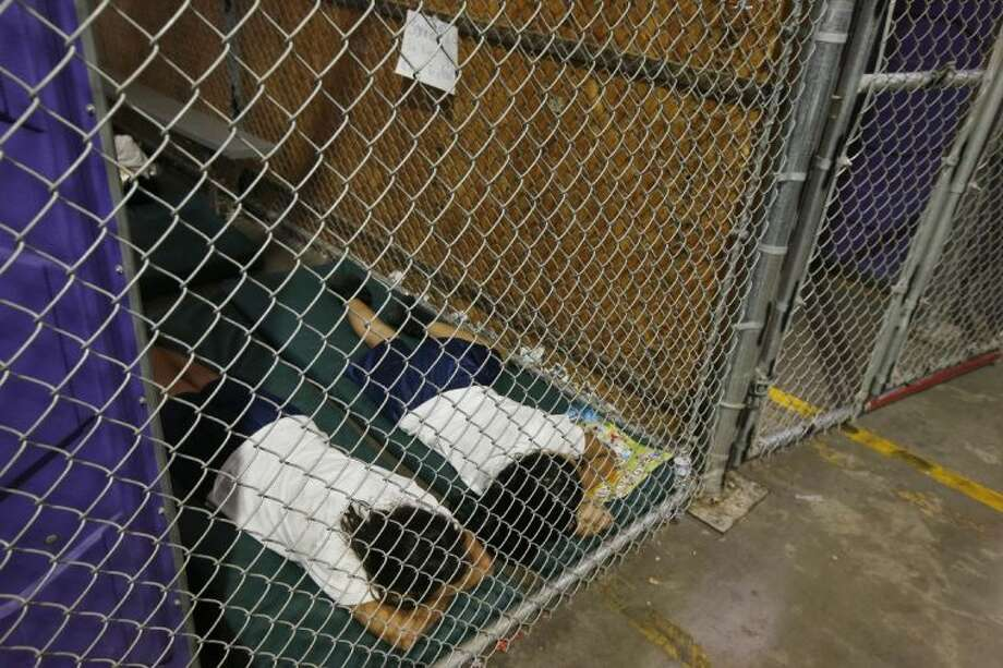 Two female detainees sleep in a holding cell, as the children are separated by age group and gender, as hundreds of mostly Central American immigrant children are being processed and held at the U.S. Customs and Border Protection Nogales Placement Center on Wednesday, June 18, 2014, in Nogales, Ariz. CPB provided media tours Wednesday of two locations in Brownsville, Texas, and Nogales, that have been central to processing the more than 47,000 unaccompanied children who have entered the country illegally since Oct. 1. (AP Photo/Ross D. Franklin, Pool) Photo: Ross D. Franklin
