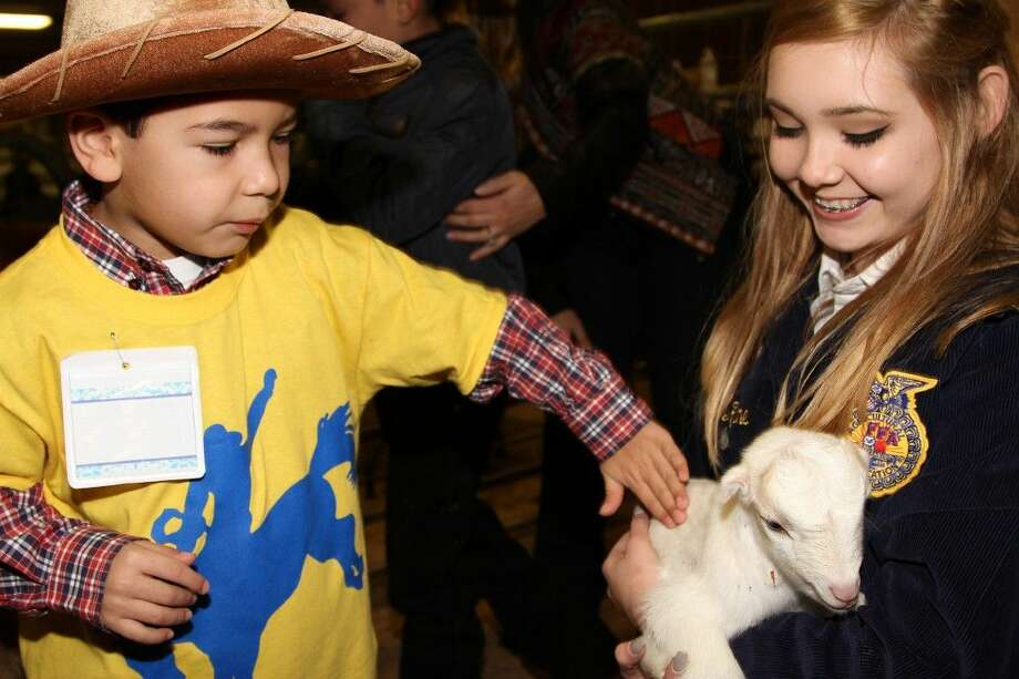 Tomball Memorial High School sophomore Jordan Keene held a baby goat at the petting zoo during Tomball ISD's 2nd Annual Special Rodeo. Sebastian Ruiz, kindergarten, Canyon Pointe Elementary, enjoyed petting several animals including potbelly pigs, baby calves, lambs, and a donkey. Photo: Submitted