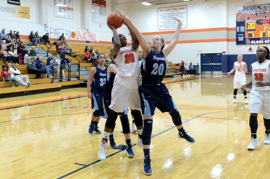 Seven Lakes' Hadassah Benenoch (30) shoots against Kingwood as Michelle Fokam (32) positions for a rebound during a Nov. 24 non-district game at Seven Lakes High School. The Lady Spartans clinched a share of their fifth consecutive district title Feb. 5. To view or purchase this photo and others like it, visit HCNpics.com. Photo: Craig Moseley