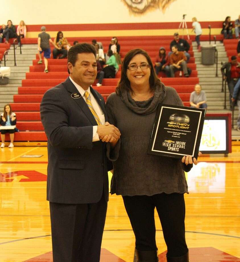Johnnie Smith, general manager for Lone Star Chevrolet, presents the Chevrolet Spotlight Award to Cypress Woods High School Director of Instruction Kelly Ellis on Feb. 5 during halftime of the Lady Wildcats' basketball game. (Photo by Matthew Ramos, Cypress Woods HS)