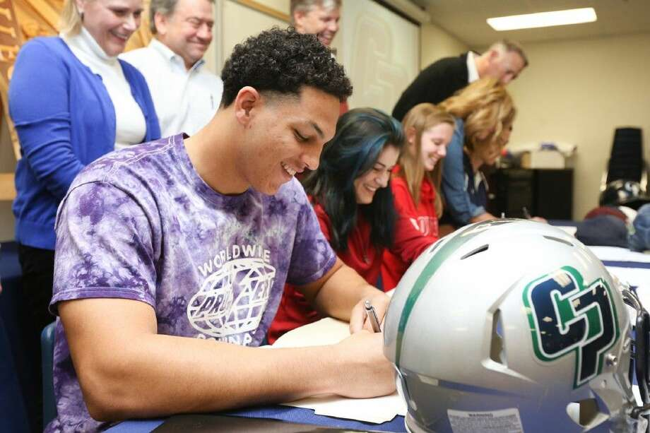 College Park's John Love signs with Ouachita Baptist University during a Signing Day ceremony on Wednesday at College Park High School.