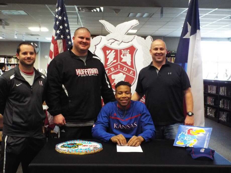 Huffman's Antione Frazier is joined by his coaches as he signs with Kansas on Wednesday, Feb. 3, 2016.