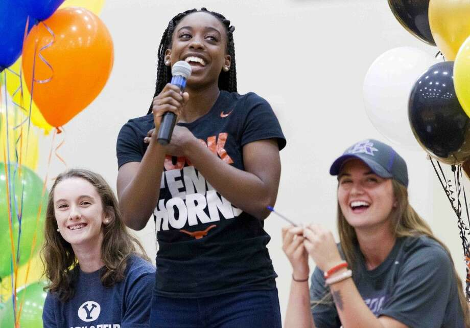 The Woodlands' Tessa Mpagi, center, laughs along side Ellyana Long, left, and Leah Starkweather during a signing day ceremony Wednesday. Mpagi signed to run track for the University of Texas.