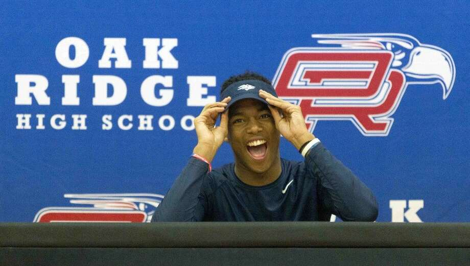 Oak Ridge's Daylon Johnson reacts as the crowd cheers during a signing day ceremony Wednesday.