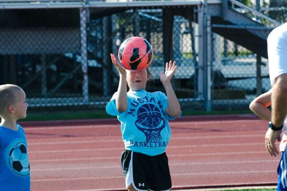 Kynadee Zamora learns how to head the soccer ball at the Friendswood High School summer soccer camp Thursday, Jun. 11. Photo: KIRK SIDES
