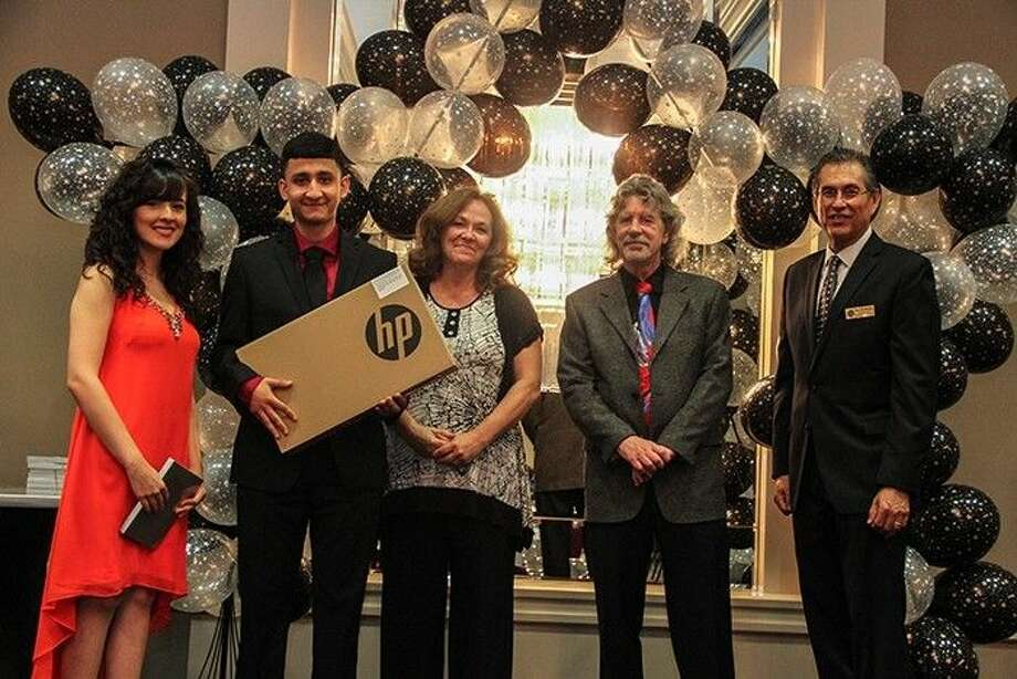 Sam Rayburn High School Senior Enrique Callado accepts his new laptop from MDL Enterprises, Inc. From l-r: Sam Rayburn High School teacher Betsy Gonzalez; Callado; MDL Enterprises co-founders Michele and Dennis Lamm and Pasadena Education Foundation President Rick Guerrero.