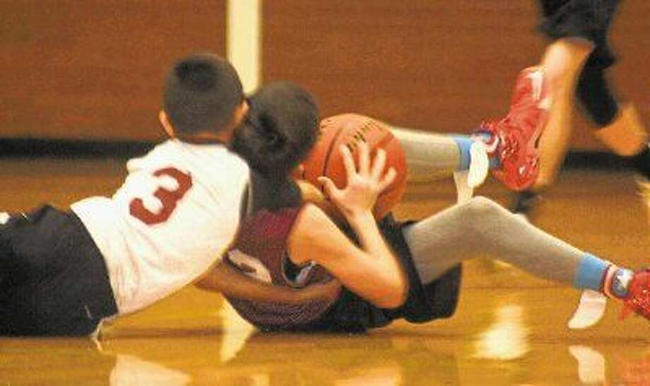 The Triple Threats' Andrew Aguilar (3) and the Bad Boyz' Ty Shephard wrestle for the basketball during their 12-and-under division contest last Saturday afternoon at Deepwater Junior High. The winner wasn't decided until a last-second shot missed its mark. Photo: Robert Avery