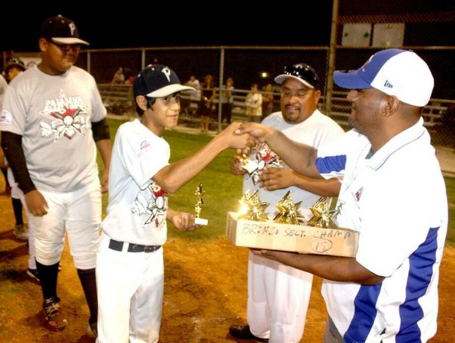 Members of the city's Bronco All-Stars accept their first-place trophies following their big win over Meadows Place at Spiller Field this past week. About to accept his trophy is starting and winning pitcher Angel Lerma. Photo: Robert Avery