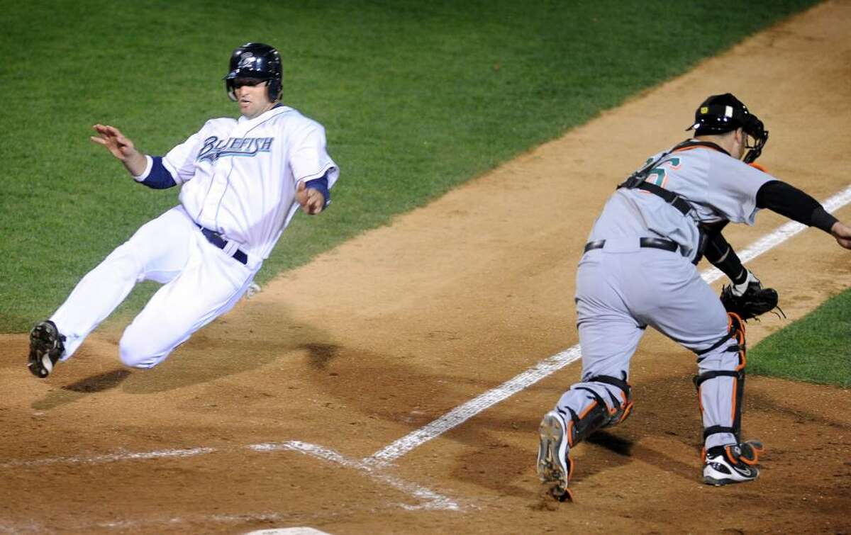 Bridgeport's Steve Moss slides home on an error in the fourth inning as Long Island catcher Tom Pennino waits for the ball Friday May 7, 2010 at the Ballpark at Harbor Yard in Bridgeport.