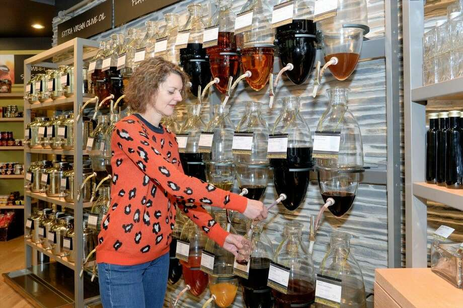 Gaby Moidel fills one of the beautiful glass containers with a tasty grapeseed oil for a customer. The Oil and Vinegar boutique is in Memorial Mall and has been open now for a little over a year-and-a-half. Photo: Craig Moseley