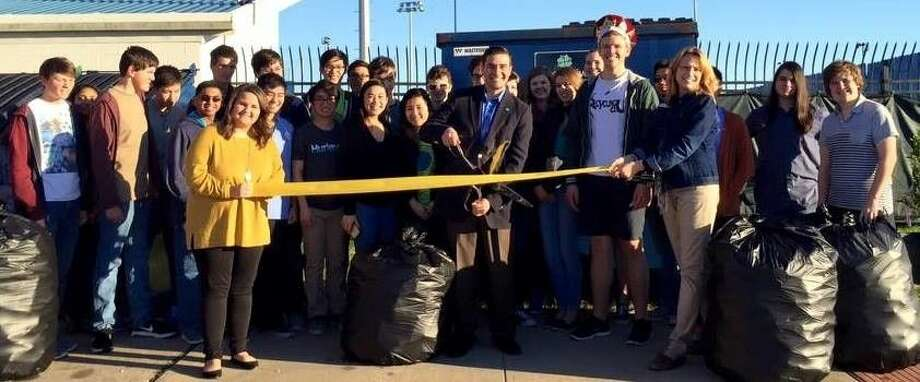 Friendswood High School Recycling Club members surround Chris Ochoa, Municipal Marketing Manager for Progressive Waste Solutions, as he cuts the ribbon at the school's first recycling container.