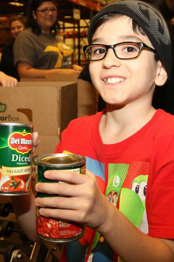 Jesus Salinas, Mae Smythe fourth grader, sifts through boxes for canned food items.