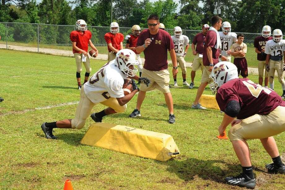Magnolia West head coach Shawn Bell oversees two of his players duriing a tackling drill. West used the spring season to beomce more physical. Photo: Tony Gaines