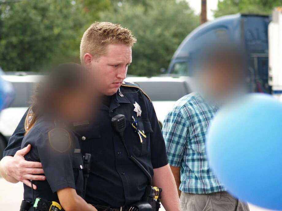 Deputy Goodrich is shown here consoling another deputy at the memorial site set up for Deputy Darren Goforth. Goodrich was fired Friday for inappropriate communications with witnesses.