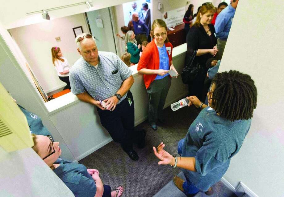Visitors learn about the services that will be offered to homeless youth at the Community Youth Outreach Youth Resource Center grand opening in Conroe on Thursday.