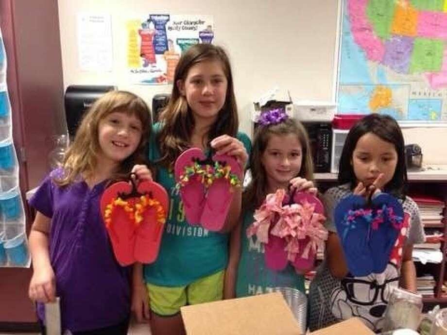 Students display decorative flip flops for sale.