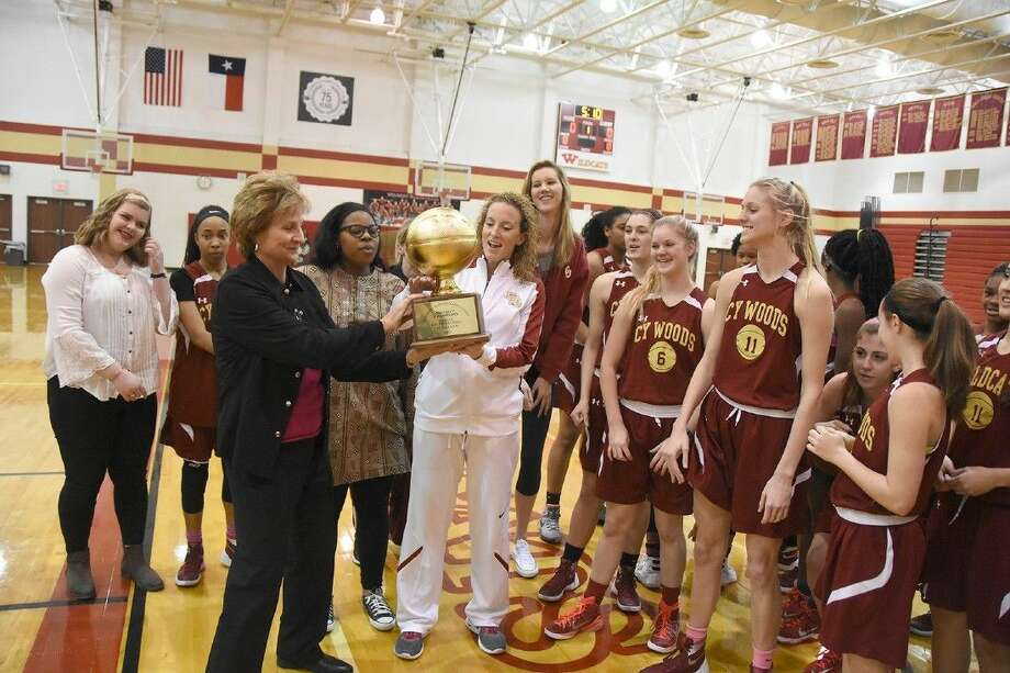 Sharon Farrah, associate director of athletics, presents the District 17-6A championship trophy to Coach Virginia Flores and the Cypress Woods High School Lady Wildcats basketball team after it completed a 13-0 district season.