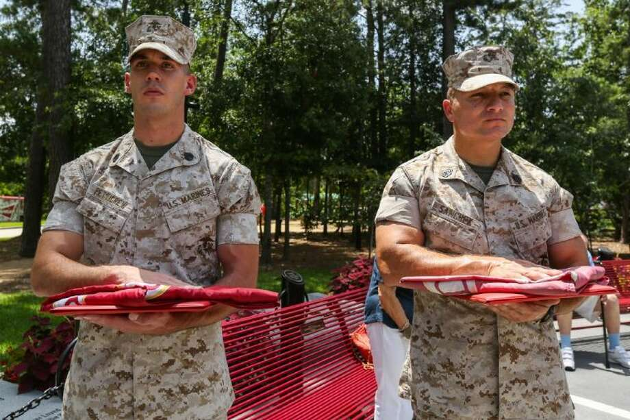 Newly promoted Marines, Staff Sgt. Andrew Petticrew, left, and Gunnery Sgt. David Sanchez, right, stand at attention during a celebratory presentation on Wednesday, July 2, at the Fallen Warriors Memorial in Houston. Photo: Michael Minasi