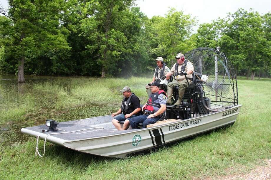 Texas game wardens Randy Button of Liberty County and Mike Boone of Hardin County, and Pct. 5 Deputy Constables David Hunter and James Gardiner leave an area in Mason Lakes that has become a boat landing. On Friday, the men were delivering water, ready-to-eat meals and snacks to residents stranded by flood waters from the Trinity River. Photo: Vanesa Brashier