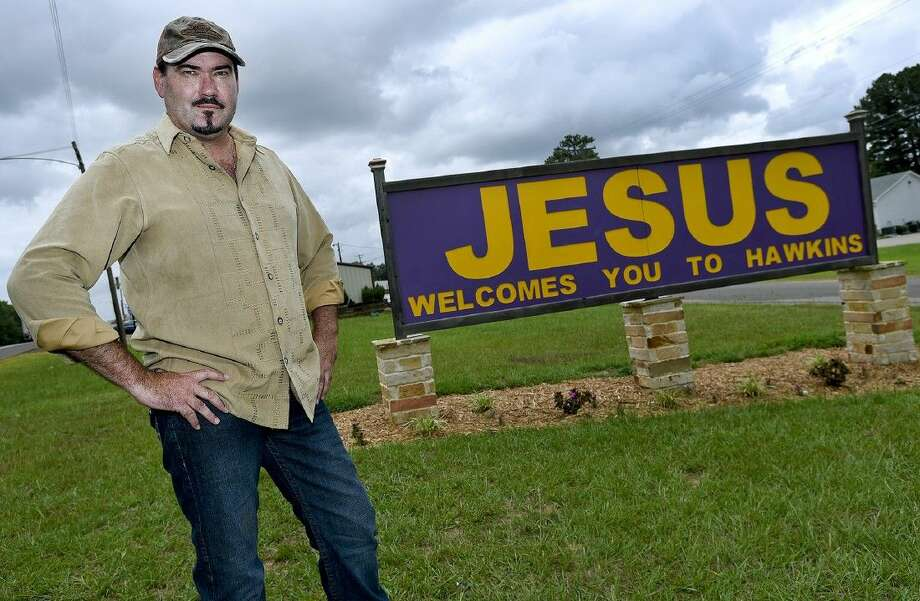 Hawkins Mayor Will Rogers poses Tuesday with a sign welcoming visitors to the small Wood County community.