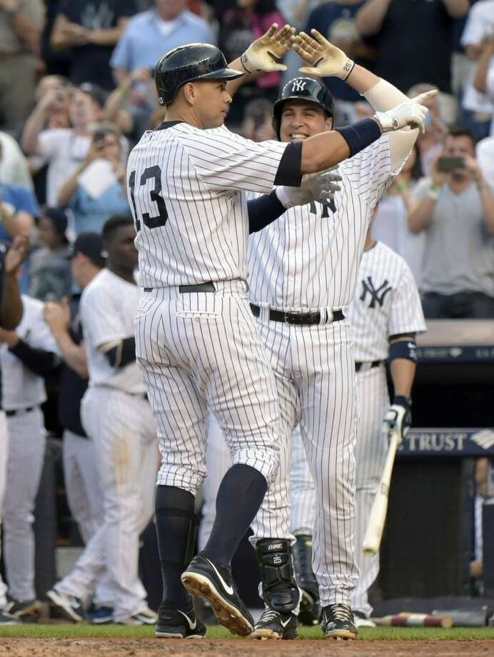 New York Yankees' Alex Rodriguez (13) celebrates with Mark Teixeira after hitting a homer run for his 3,000th career hit Friday night at Yankee Stadium in New York.