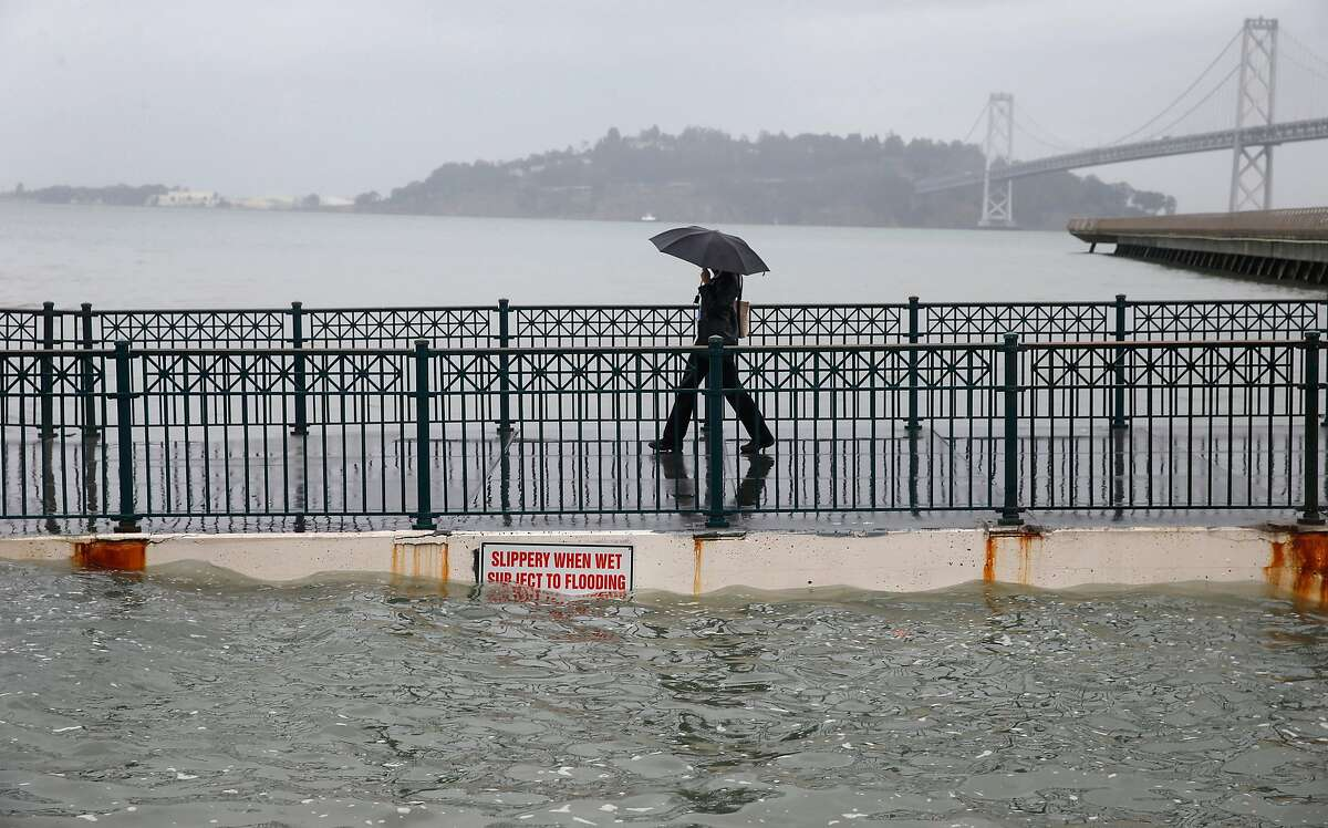 Luna Taylor walks off of Pier 14 during the peak of the high tide along the Embarcadero in San Francisco, Calif. on Tuesday, Nov. 24, 2015.