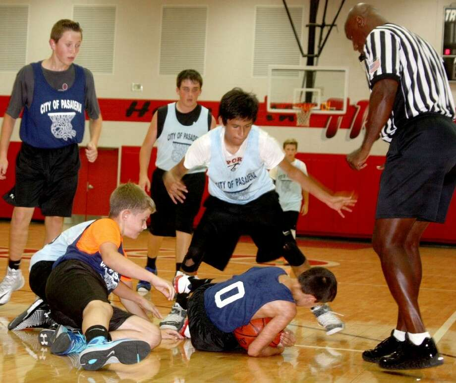 Fairmont Junior High's Tyler Jordan (0) comes up with a loose ball as La Porte Junior High players lost the scramble. The seventh-grade division contest went down to the wire with Fairmont hanging on for a 23-21 win. Photo: Robert Avery