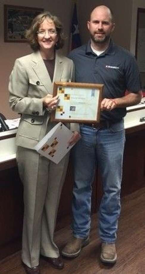 Splendora ISD Superintendent Genese Bell awarded a certificate to Kennedy Fabricating, Inc. owner Kevin Kennedy during the Feb. 15 Splendora ISD school board meeting. The business was recognized for its extensive work with the district. Photo: Submitted