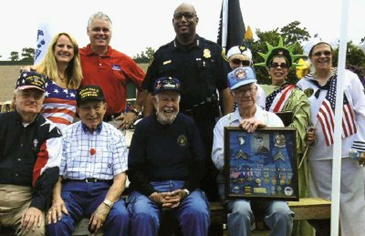 Texas State Rep. Dan Huberty, wife Janet, and Houston Police Chief Charles McClelland pose with a number of World War II vets prior to the parade start.