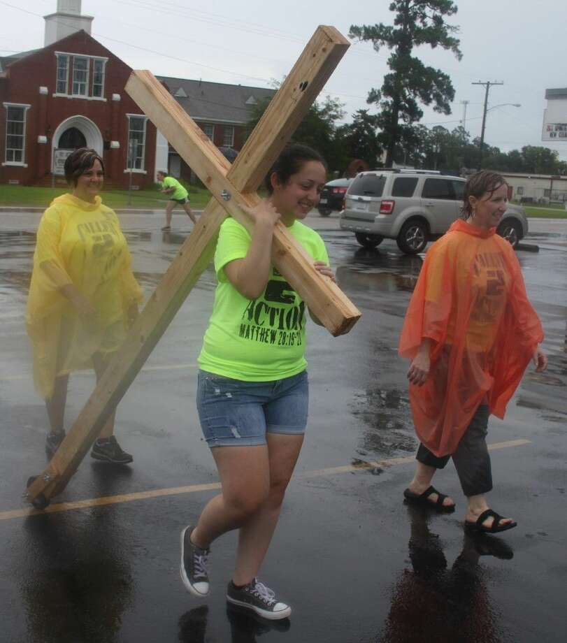 Haylee Kersh (middle) returns to the Covenant of Christ Resale Shop after carrying a cross around town and accompanied by Shaeilaine Asfour (left) and Christie Chamberlain (right). Photo: Jacob McAdams