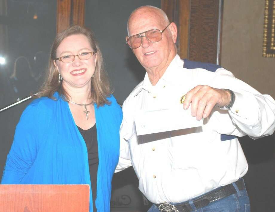 Rotarian of the Month of May Ed Brantley accepts a check for $421 benefiting Sara's House. This money came from bowls at each table at each meeting, to which members make contributions.