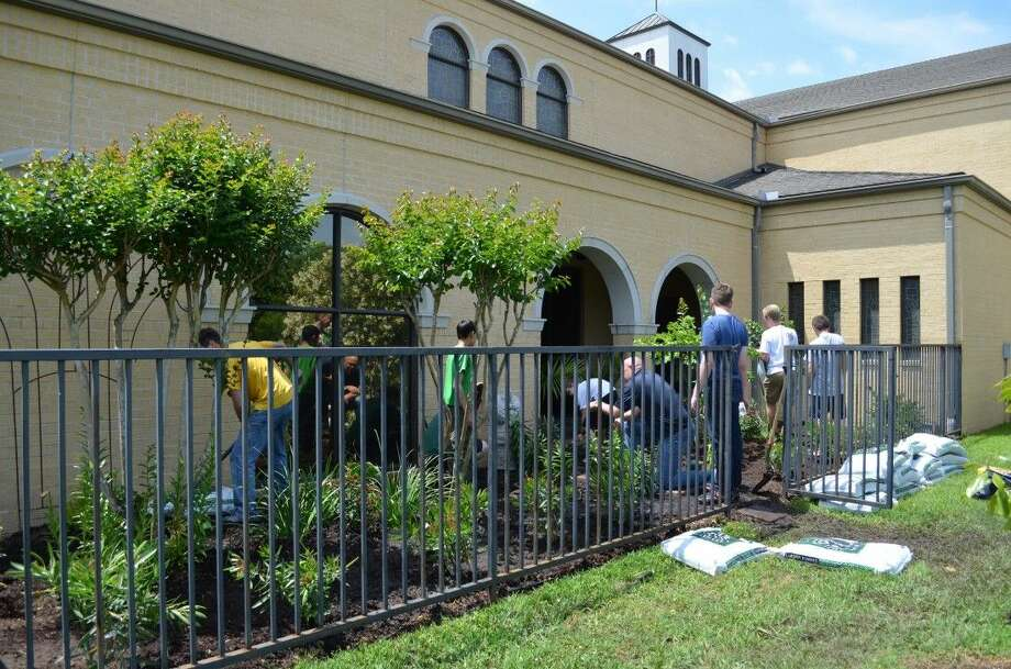 Members of Boy Scout Troop 432 chartered by the Baybrook Ward of The Church of Jesus Christ of Latter-day Saints restoring a garden at St.Mary's Catholic Church in League City as part of Aaron Lassmann's Eagle Scout Project.