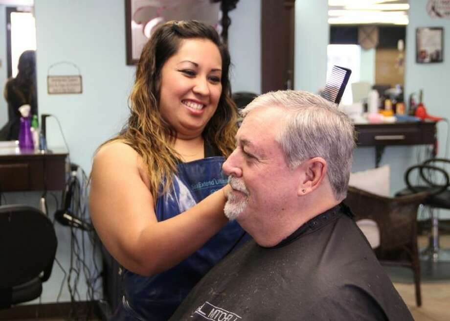 Yvonne Flores styles a customer's hair at Envy Salon in Texas City. The College of the Mainland cosmetology graduate works with three other COM grads as independent stylists at the salon, which has an addition under construction. Photo: Courtesy College Of The Mainland