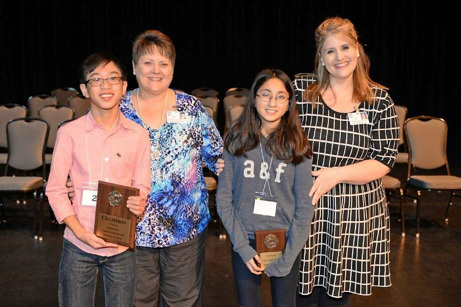 Middle School Spelling Bee winner Gabriel Bolanos, left, of Aragon Middle School and runner-up Asha Lamba of Truitt Middle School display their plaques alongside Sarah Price, secondary English language arts technology curriculum coach, and Ami Ruby, coordinator for secondary English language arts.