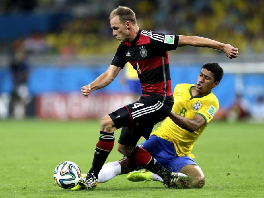 Germany's Benedikt Höwedes works against Brazil's Paulinho during a World Cup semifinal match on Tuesday at Estádio Mineirão in Belo Horizonte, Brazil.